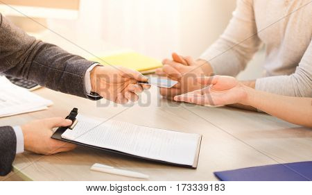 Closeup toned of salesman or businessman giving credit card to couple and offering agreement or contract for signing.