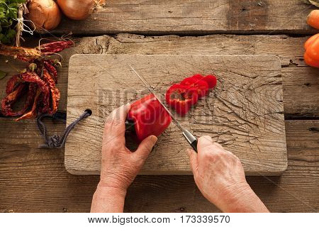 Woman's hands slicing pepper on wooden board cooking lunch for vegetarians. Cooking healthy food with vitamins.
