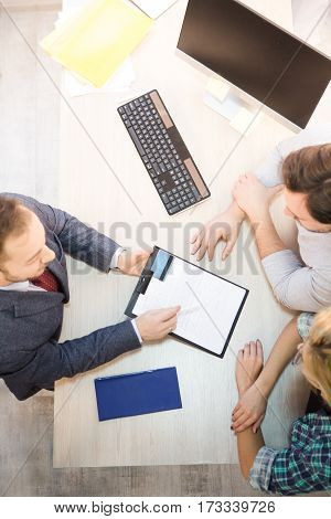 Top toned of salesman or manager offering agreement or contract for young couple. Man asking people to sign and to get credit card. Bank officer.