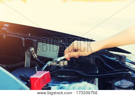 Asian women's hand or mechanic checking car battery.