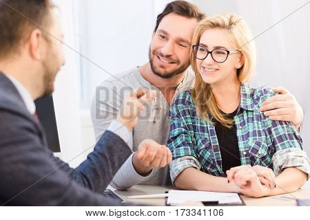 Toned of sales manager giving key to young couple in love. Happy couple smiling after signing agreement or contract for purchase or sale. Dealership concept.