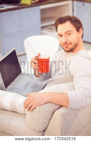 Toned of freelance man working on laptop computer at home and drinking coffee while sitting on sofa or couch. Business concept. Freelance concept.