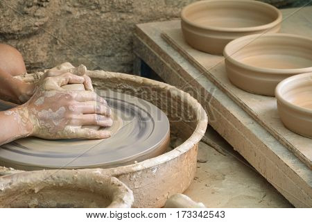 Detailed view of craftsman hands working on pottery wheel, young woman