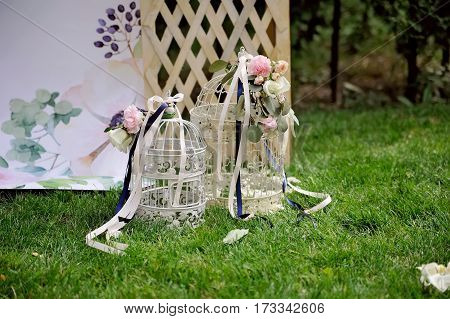 Beautiful birdcage decorated with flowers and ribbons, staying on grass, outdoor