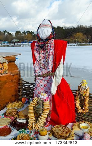 Shrovetide doll in colorful costume near table with samovar pancakes and bagels