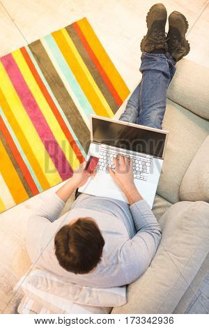 Freelance or business concept. Top toned of handsome man working on laptop computer and holding credit card while sitting on sofa or couch at home.