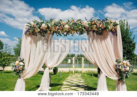 Beautiful wedding archway. Arch decorated with biege cloth and flowers