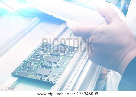 Computer expert professional technician examining board computer in a laboratory in a factory. The concept of high computer technologies and innovations. Conceptual image.