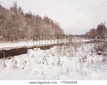 River bend in winter. Typical winter landscape in contryside. Snowy wether.  Unfrozen blue water.