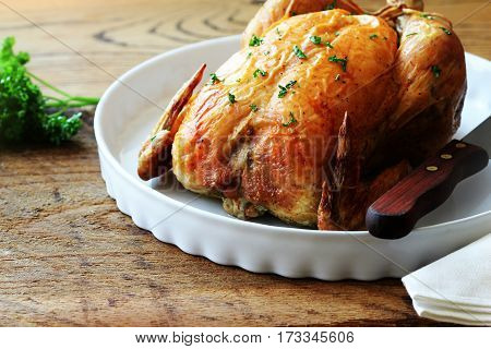Roasted chicken with herbs on wooden background