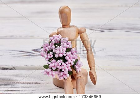 Wooden manikin holding flowers. The idea of an apology.