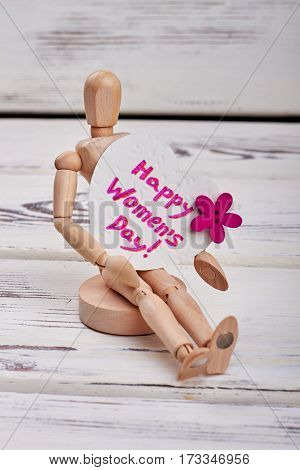 Wooden manikin and heart-shaped card. Greeting for woman.