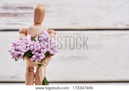 Manikin with bunch of flowers. Romantic good morning.
