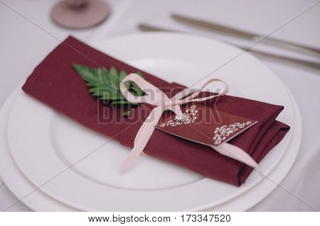 Decorated with green petal and tied up with pink bow, dark red napkin