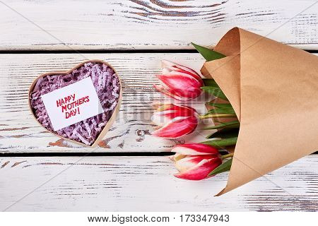 Heart-shaped box and flowers. Congratulation for dear mother.