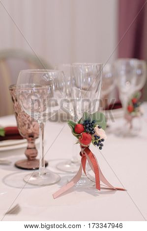 Decorated with flowers boutonniere wine and champagne glasses