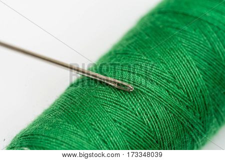 Needle Head On The Green Thread Over White Background