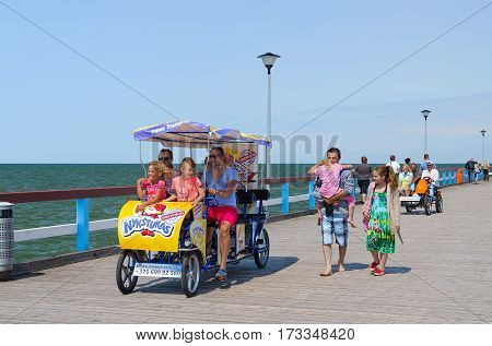 PALANGA LITHUANIA - JULY 12 2015: Unidentified people walk on famous pier in popular resort town of Palanga Lithuania