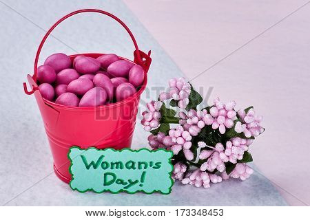 Flowers and bucket with candies. Surprise for dear women.