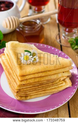 Stack of thin crepes for breakfast with daisy camomiles
