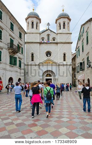 KOTOR MONTENEGRO - SEPTEMBER 21 2015: Group of unidentified tourists are near church of St. Nicholas on square of Old Town Kotor Montenegro