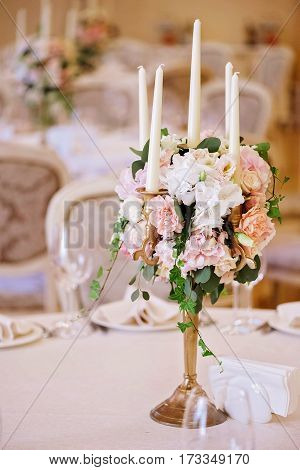 Guest tables with candlestick in luxury decorated wedding banquet room