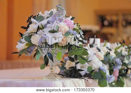 Beautifully decorated bouquet of white and pink roses, peons, petals, berries and green petals in glass vase