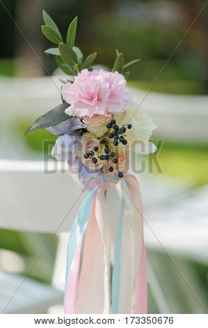 Pink peon and roses buds in tenderless boutonniere, with biege and pink ribbons, closeup