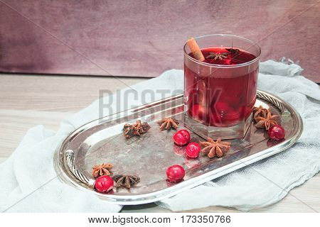 mulled wine with cherries cinnamon and star anise in a glass on vintage silver tray
