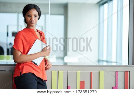 Businesswoman wearing a bright orange blouse and holding a digital tablet while standing in a colourful business environment, looking straight into the camera.