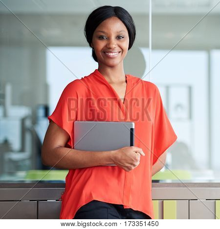 Square portrait of black entrepreneur holding a digital tablet while smiling happily at the camera wearing a bright orange shirt while standing in her usual business environment.
