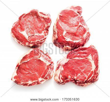 four raw rib-eye beaf steaks isolated on white background