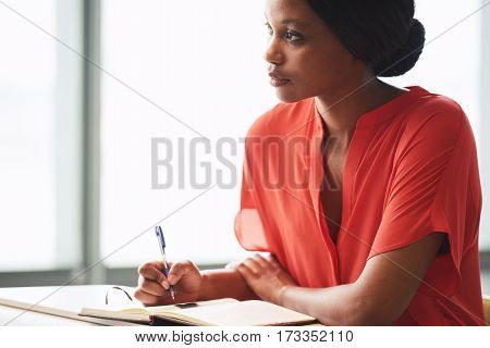 Black female creative writer busy looking up into the distance as she procrastinates and takes a break from her writing session while dressed in a colourful orange shirt.
