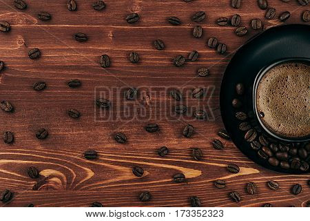 Hot coffee in black cup with crema and pattern beans with copy space on brown old wooden board background top view. Rustic style.