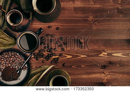 Hot coffee in black cup and several turkish pots cezve with beans dry leaves with copy space on brown old wooden board background top view. Rustic style.