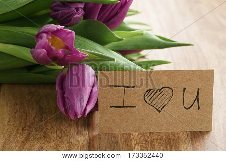 bouquet of purple tulips on wood table with i love you greeting card shallow dof