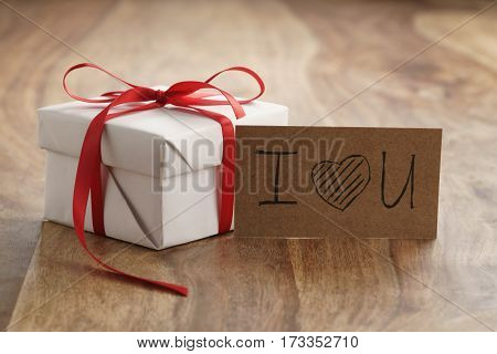 white paper gift box with thin red ribbon bow on old wood table, with i love you paper card