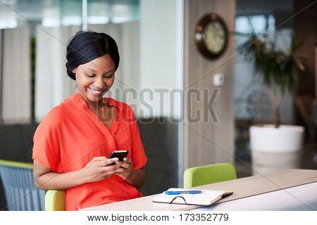 black woman using the phone she is holding in her hands to type text messages to colleagues with a large smile on her face while seated in a colourful business lounge.