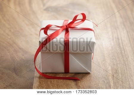 white paper gift box with thin red ribbon bow on old wood table, closeup photo