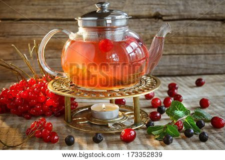 Red colorful tea. Glass tea pot with hot tasty tea with lemon, herbs and many red, yellow berries,. Berries, greens, mint and tea. Tea pot on warm colors on wooden background. Hot tasty tea wit mint