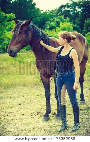 Jockey Woman Walking With Horse On Meadow