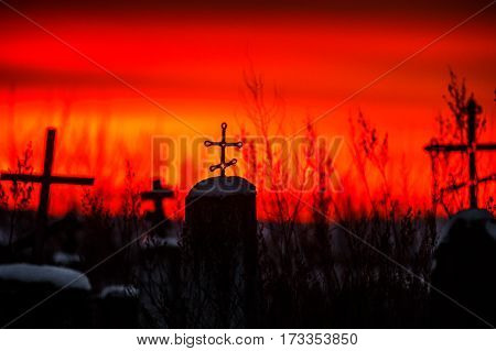Christian cross silhouette with the bloody sunset as background