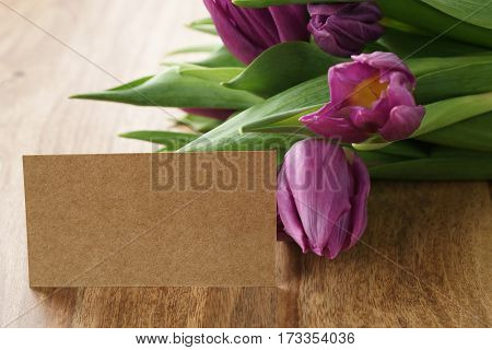 bouquet of purple tulips on wood table with copy space on paper card, shallow focus