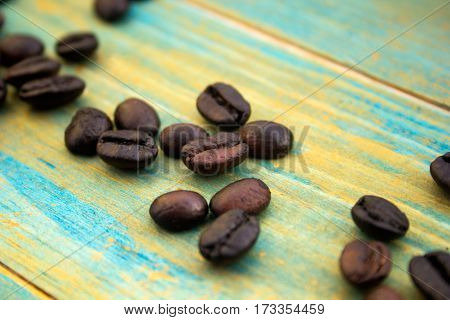 coffee beans on wooden background painted in blue and gold. close-up.