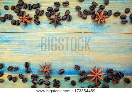 coffee beans and anise stars on wooden background painted in blue and gold. place for text.
