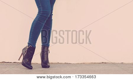 Autumn fashion outfit. Fashionable woman long legs in denim pants black stylish high heels shoes outdoor on street