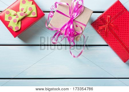 Colorful gift boxes on nice blue wooden background with free space.