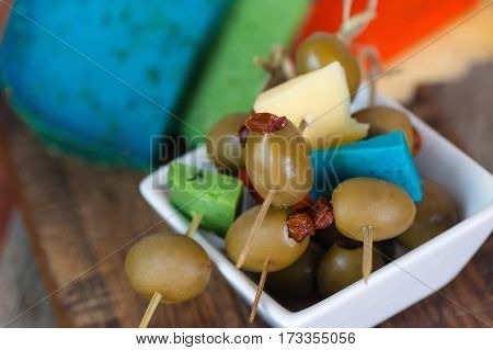 Canape with olives and colorful cheese on wooden background.