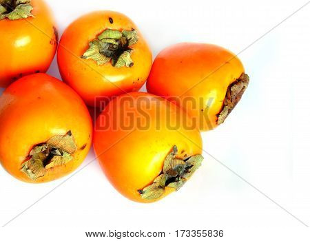 Still life with five ripe big persimmons isolated studio shot top view closeup