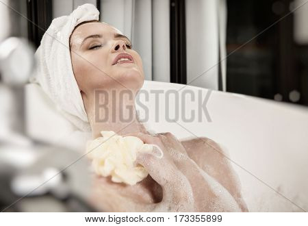 Red-haired beautiful young woman with a towel on her head after bath. Concept of care of body.